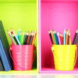 Colorful pencils in pails with writing-pad on shelves — Stock Photo #24277235