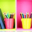 Colorful pencils in pails with writing-pad on shelves — Stok fotoğraf