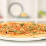 chutné pizzy na štítku na pozadí kuchyně — Stock fotografie