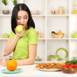 Pretty girl selects pizzor diet on kitchen background — Stock Photo #24278129