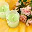 Candles on a yellow fabric close-up - Foto Stock