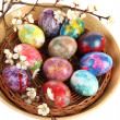 Beautiful Easter eggs in wicker basket isolated on white — Stock Photo #24278553