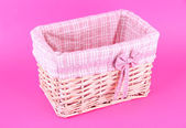 Wicket basket with pink fabric and bow, on color background — Stock Photo