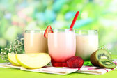Delicious yogurts with fruits in glasses on wooden table on natural background — Stock Photo