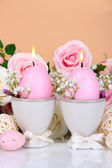 Easter candles with flowers on beige background — Stock Photo