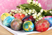 Easter eggs on wooden plate on napkin with flowers close-up — Stock Photo