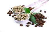 Green and brown coffee beans in wooden spoons and leaves isolated on white — Stock Photo