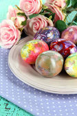 Easter eggs on plate with napkin and flowers close-up — Stock Photo