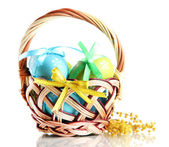 Easter eggs in basket and mimosa flowers, isolated on white — Stock Photo