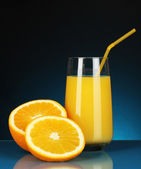 Delicious orange juice in glass and oranges next to it on dark blue background — Stock Photo