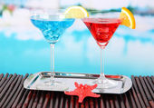 Glasses of cocktails on table near pool — Stock Photo