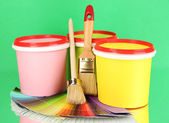 Set for painting: paint pots, brushes, palette of colors on green background — Stock Photo