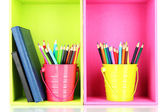 Colorful pencils in pails with writing-pad on shelves — Stock Photo