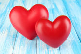 Decorative red hearts on color wooden background — Stock Photo