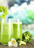Glasses of vegetable juice, on bamboo mat, on green background — Stock Photo