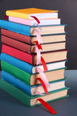 Many books with bookmarks on gray background — Stock Photo