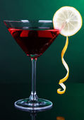 Red cocktail in martini glass on dark green background — Stock Photo