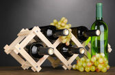 Bouteilles de vin placé sur un socle en bois sur fond gris — Photo