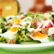 Fresh mixed salad with eggs, salad leaves and other vegetables, on bright background — Stock Photo #24280635