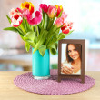 Beautiful tulips in bucket on table in room — Stock Photo