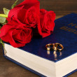 Wedding rings on bible with roses on wooden background — Stock Photo #24280991