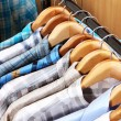 Men's shirts on hangers in wardrobe - Stock Photo