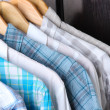 Men's shirts on hangers on wooden background - Stock Photo