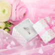 Ranunculus (persian buttercups) and engagement ring, on pink cloth — Stock Photo