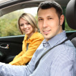 Portrait of young beautiful couple sitting in the car — Stock Photo #24282133