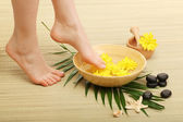 Female feet in spa bowl with water, on bamboo mat — 图库照片