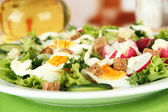 Fresh mixed salad with eggs, salad leaves and other vegetables, on bright background — Stock Photo