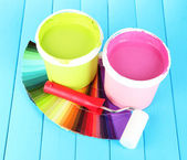 Set for painting: paint pots, paint-roller on blue wooden table — Stock Photo