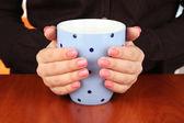 Hände halten Tasse warm trinken, close-up — Stockfoto