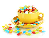 Colorful candies in cup isolated on white — Stock Photo