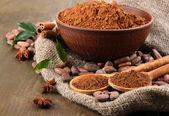 Kakaopulver und kakaobohnen auf hölzernen hintergrund — Stockfoto