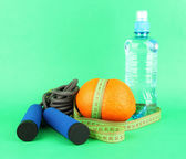 Orange with measuring tape,skipping rope and bottle of water, on color background — ストック写真
