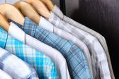 Men's shirts on hangers on wooden background — Stockfoto