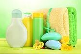 婴儿化妆品、 肥皂和毛巾上的木桌上绿色背景 — 图库照片