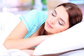 Beautiful young woman sleeping in bed — Stok fotoğraf