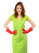 Young woman wearing green apron and rubber gloves, isolated on white — Stock Photo