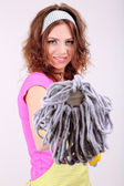 Young housewife with mop on grey background — Stock Photo