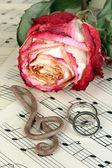 Klav, rose och vigselringar på musikaliska bakgrund — Stockfoto