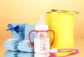 Bottle with milk and food for babies on beige background — Stock Photo