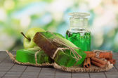 Hand made soap and ingredients for soap making on bamboo mat, on green background — Stock Photo