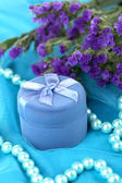 Flowers and engagement ring box on blue cloth — Stock Photo