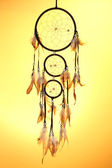 Beautiful dream catcher on yellow background — Stockfoto