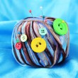 Colorful buttons and multicolor wool balls, on color fabric background — Stock Photo