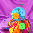 Colorful buttons and multicolor wool balls, on color fabric background — Stock Photo #24409073