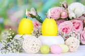 Easter candles with flowers on bright background — Стоковое фото