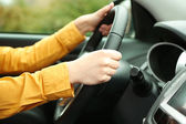 Female hands over a wheel in the car, close up — Stock Photo